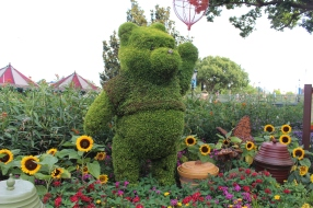 Oh bother. Pooh flanked by honey pots and dwarf sunflowers.