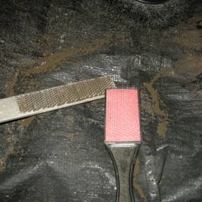 """Clean the rasp with a """"file card"""" while it's damp. It comes out easily. Once it dries, you need a chisel."""