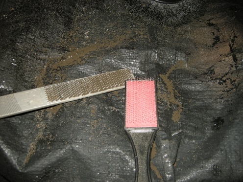 "Clean the rasp with a ""file card"" while it's damp. It comes out easily. Once it dries, you need a chisel."