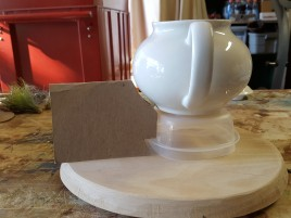 "The foundation: 3/4"" oak 11"" diameter, upside down food container, tea pot."
