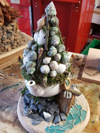 I hot glued the branches first, then filled in with shells. The pathway is sea glass.