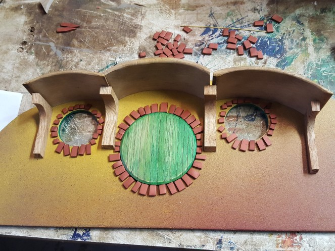 The bricks are Fimo polymer clay, copper color. Rolled, cut, baked and laid out.